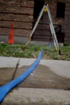 This hose emerged from the basement of one of the boarded up buildings at the Lathrop Homes.
